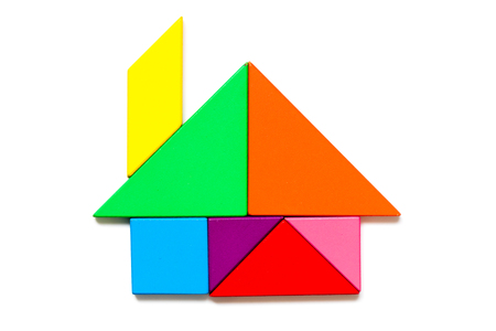 Foto de Color wood tangram puzzle in home shape on white background - Imagen libre de derechos