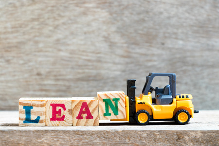 Photo pour Toy forklift hold letter block n to complete word lean on wood background - image libre de droit
