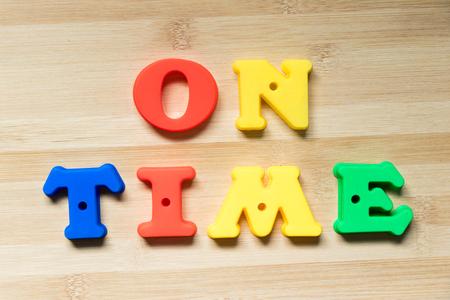 Foto de Color plastic alphabet in word on time on wood background - Imagen libre de derechos