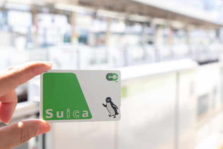 Foto de Tokyo, Japan - May 4, 2019 : Man hold Suica pass with the blurred train station background, Suica is a prepaid card for travelling with train, bus and shopping in Japan. - Imagen libre de derechos