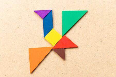 Photo pour Color tangram puzzle in flying bird shape on wood background - image libre de droit