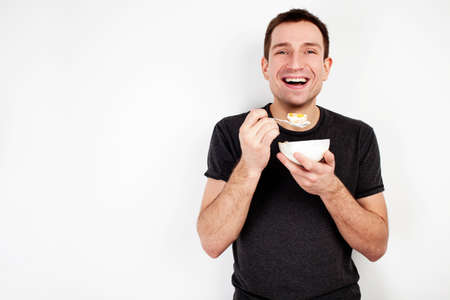 Foto per Young smiling man eating musli on diet isolated on white background - Immagine Royalty Free