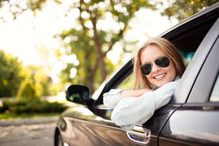 Photo pour Young woman in her new car smiling. - image libre de droit