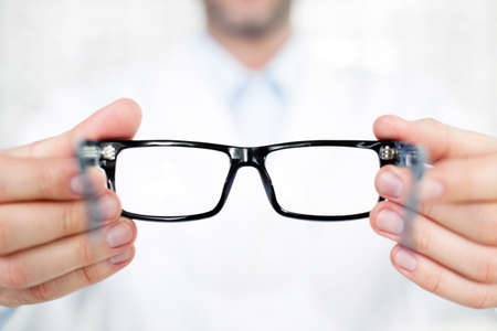 Foto de Closeup of optometrist, optician giving glasses  to try - Imagen libre de derechos
