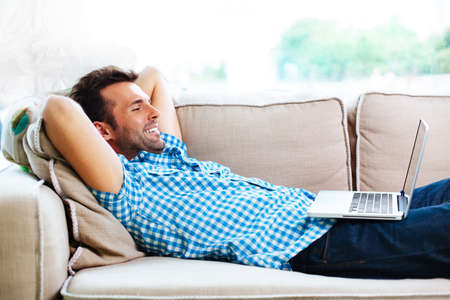 Photo pour Man relaxing with laptop on couch - image libre de droit