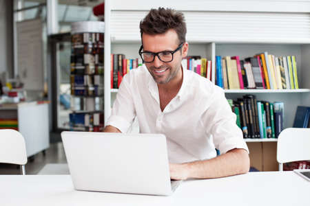 Photo for Happy man working on laptop in library - Royalty Free Image