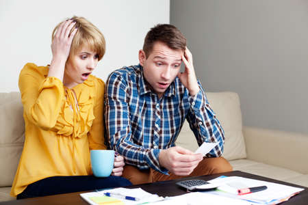 Foto de Shocked couple paying bills at home - Imagen libre de derechos