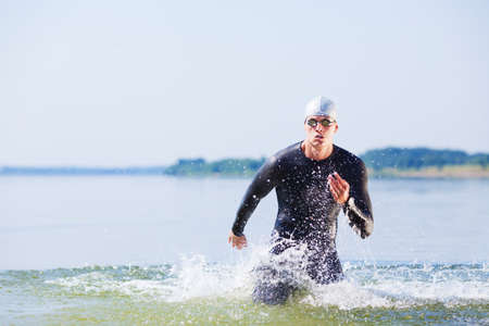 Photo pour Triathlete running out of the water on triathlon race. - image libre de droit