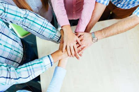 Foto de Group of corporate people working on new project joining hands over table - Imagen libre de derechos