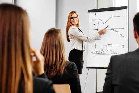Foto de Businesswoman giving presentation on flipchart. Business meeting in the office - Imagen libre de derechos