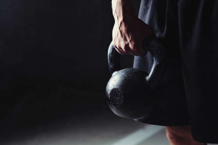 Photo pour Close-up of a muscular hand holding a kettlebell - image libre de droit