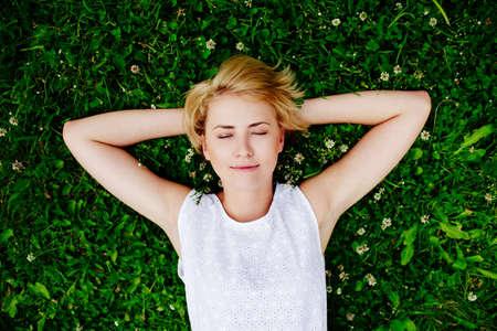 Photo pour Portrait of a young woman lying on the grass - image libre de droit