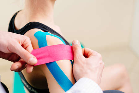 Foto de Kinesiotaping. Physical therapist applying tape to patient shoulder - Imagen libre de derechos
