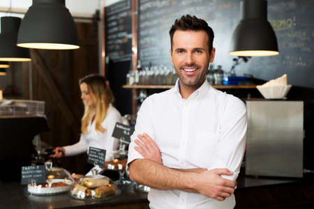 Photo for Happy small business owner standing at front of bar with employee in background preparing coffee - Royalty Free Image