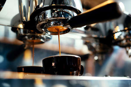Foto de Close-up of espresso pouring from coffee machine. Professional coffee brewing - Imagen libre de derechos
