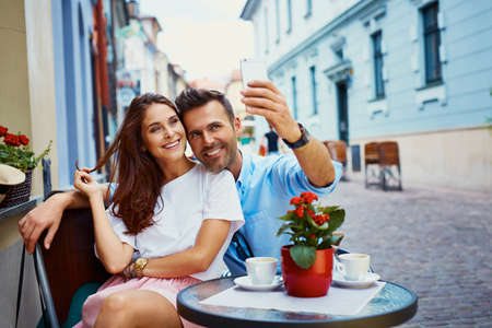 Photo pour Couple on vacation taking selfie in outdoors cafe - image libre de droit