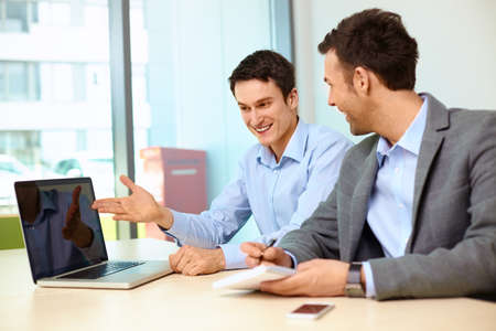 Foto de Two businessmen working on laptop in modern office - Imagen libre de derechos