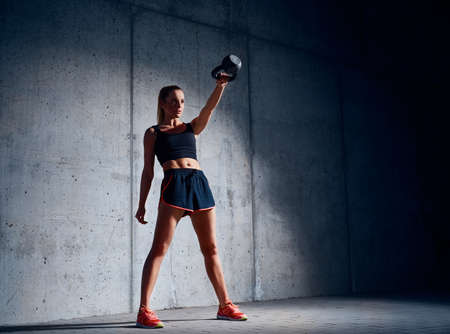 Photo for Young woman doing kettlebell swing exercise - Royalty Free Image