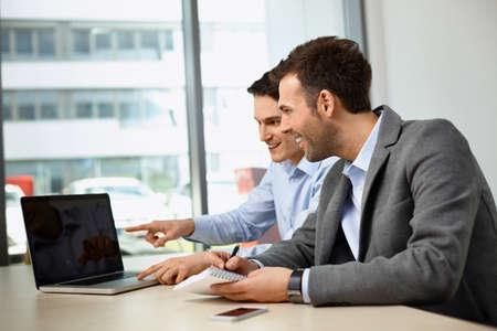 Foto de Meeting of two business man at office, discussing project on laptop - Imagen libre de derechos