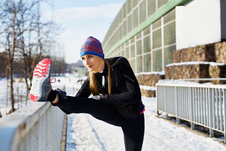 Foto de Female runner stretching before running at winter - Imagen libre de derechos
