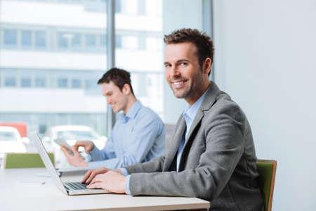 Foto de Two business people working in office, sitting by desk - Imagen libre de derechos
