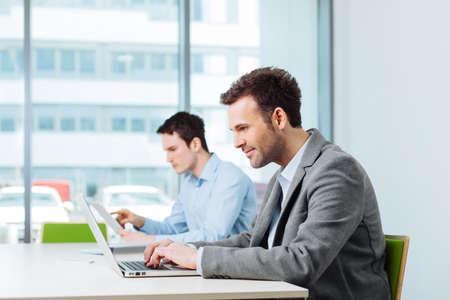 Foto de Two business people busy working in coworking office - Imagen libre de derechos