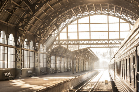 Photo pour Train station indoor sunset sunrise in sepia. Carriage and platform with construction roof. Travel on train on railway - image libre de droit