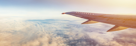 Foto per Flight wing panorama with copy space. Aircraft wing above the earth and clouds. Flight in sky. Travel by airlines for vacations. - Immagine Royalty Free