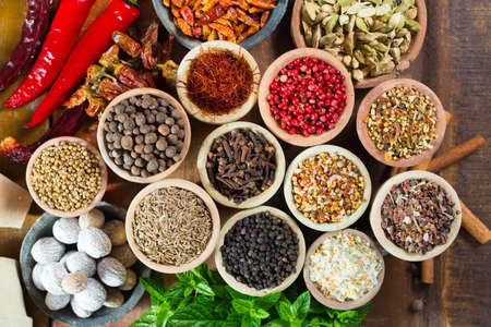 Photo for Variety of different asian and middle east spices, colorful assortment, on old wooden table, close up - Royalty Free Image
