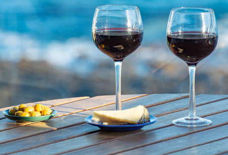 Photo pour Aperitif, red wine in glasses served with cheese and olives on outdoor tessace witn sea view close up - image libre de droit