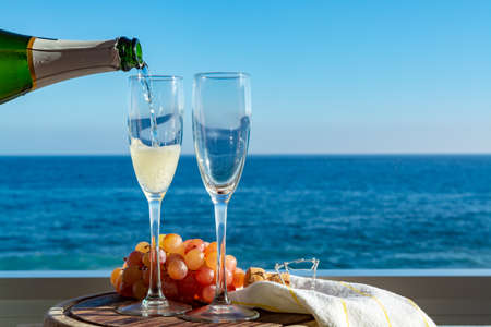 Foto de Waiter pouring Champagne, prosecco or cava in two glasses on outside terrace with sea view  close up - Imagen libre de derechos