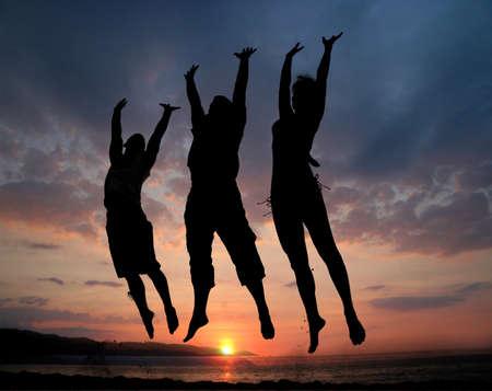 Foto de Three people silhouettes jumping on the beach - Imagen libre de derechos