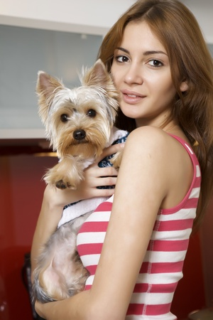 Cute young brunette girl with her Yorkshire terrier puppy lying on sofa