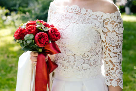 Photo pour wedding bouquet of burgundy roses in the hands of the bride - image libre de droit
