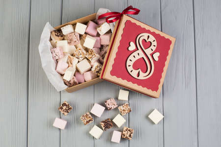 Photo for Assorted marshmallow on grey wood table with gift box for eight march - Royalty Free Image