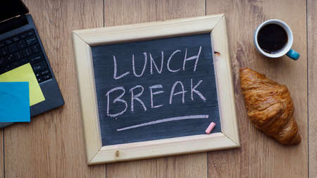 Photo for Lunch break written on a chalkboard next to a breakfast at the office - Royalty Free Image