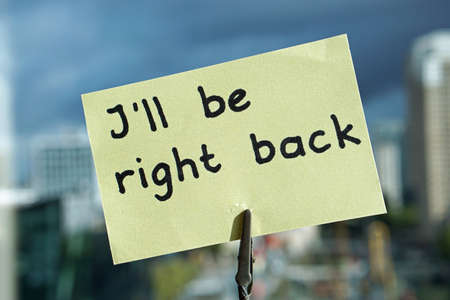 Foto de I'll be right back at the office written on a memo at the office in a city          - Imagen libre de derechos