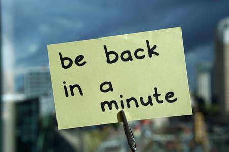 Foto de be back in a minute written on a memo at the office in the city                          - Imagen libre de derechos