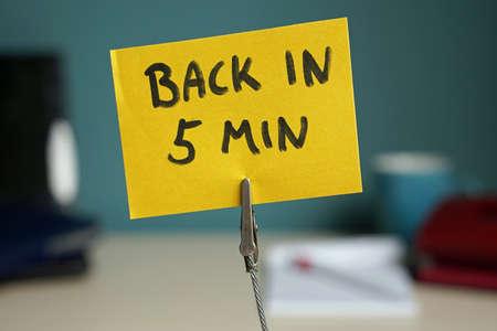 Foto de Back in 5 min written on a memo at the office - Imagen libre de derechos