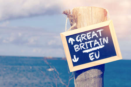 Photo for Sea, beach and a sign with directional arrows to the UK and European Union EU - Royalty Free Image