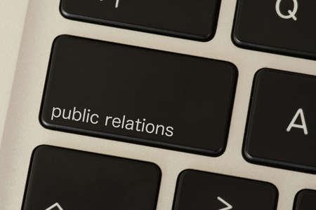 Foto de A computer and a public relations button - Imagen libre de derechos