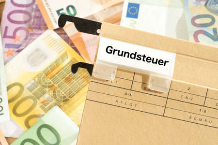 Foto de Euro banknotes and a folder with the imprint property tax - Imagen libre de derechos