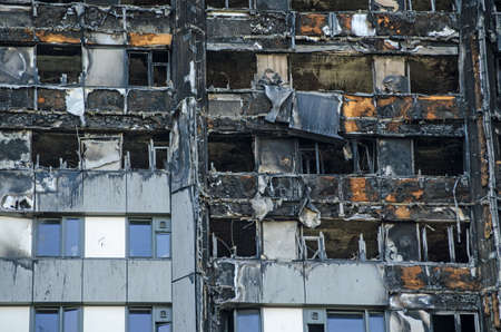 Foto de Close up view of the exterior of the Grenfell Tower block of flats in which at least 80 people lost their lives in a fire.  Remains of exterior cladding can be seen out the outside of the building, this is thought to have increased the spread of the fire. - Imagen libre de derechos