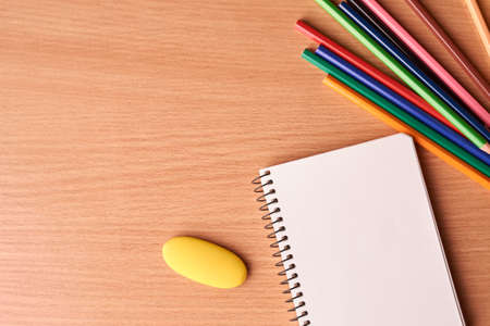 Photo for blank notebook page with colored pencils on table on black background - Royalty Free Image