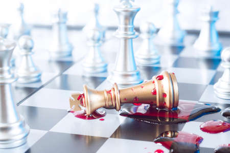 Foto de A conceptual photo with chess pieces and blood on a chessboard. Business, law or political concept, which could represent the war of corporations, geopolitical situation and so on. Selective focus. - Imagen libre de derechos
