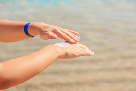 Foto de Women's hands apply a suntan lotion to the skin, protect from the sun. - Imagen libre de derechos