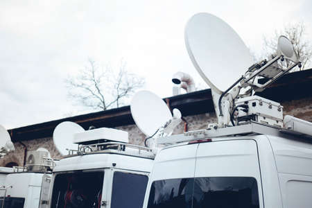 Foto de TV Media Television Trucks with multiple Satellite parabolic antennas and fiber optic cables preparing to report live a political sport or other news event - Imagen libre de derechos