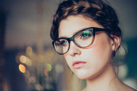 Photo pour Portrait of pretty young woman wearing glasses. Professional make-up and hairstyle. Perfect skin. Fashion photo. - image libre de droit