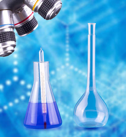 Foto de Laboratory flaskes with thermometer and microscope on a blue background - Imagen libre de derechos