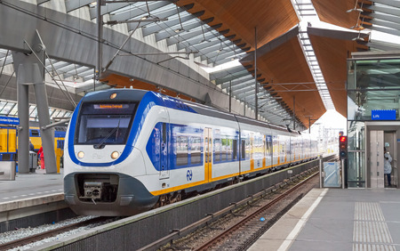 Amsterdam, Netherlands - June 23, 2014: White-blue shuttle train stays on Amsterdam Arena rail station